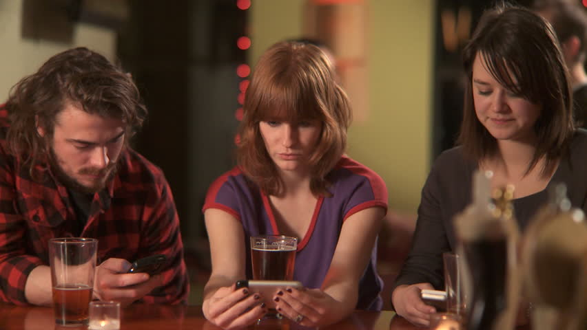 MS, PAN, Selective Focus, Three friends sitting at a bar using their mobile phones
