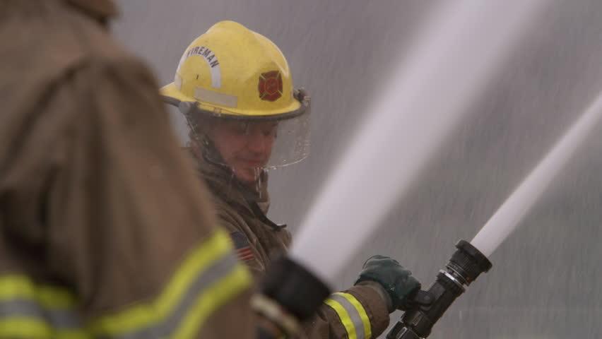 Fireman spraying water from a high pressure hose   Shutterstock HD Video #26508938