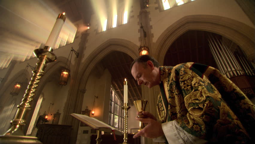 Priest making the sign of the cross over the chalice during Eucharist
