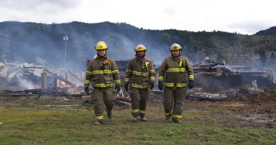 Slow-motion shot of three firemen walking towards the camera with a smoldering structure in the background