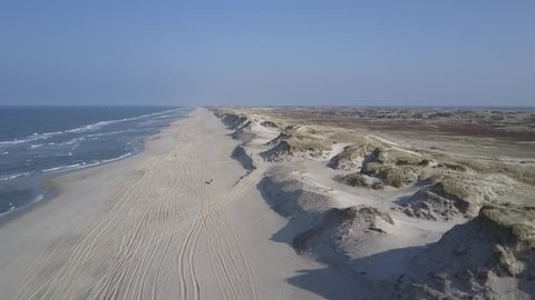 Aerial, flight over grass covered dunes along the beach on Denmarks North Sea coast