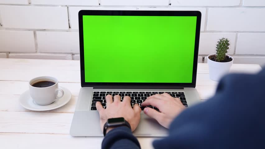 A man working on a laptop on his desk with phone. Green screen for your custom screen content. | Shutterstock HD Video #26517665