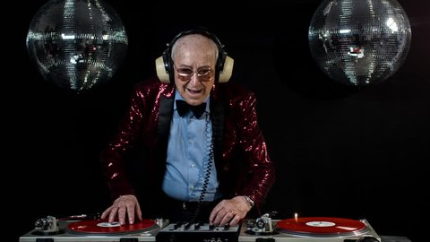 amazing DJ grandpa, older man djing and partying in a disco setting. these retired rockers will get the party going