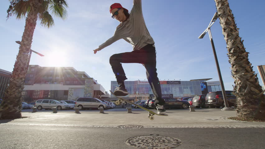 KOPER, SLOVENIA, December 26, 2016, SLOW MOTION: skateboarder riding skateboard along the palm tree avenue, jumping and performing freestyle tricks. Skater with skills doing ollies and spins
