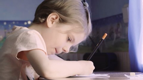 Little girl writing and drawing. Doing homeworks. Child. Adorable girl.