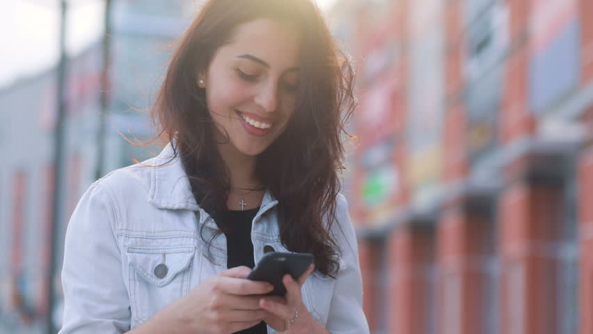 Attractive brown-haired caucasian girl staying in the sun in front of shopping mall and using her smartphone, looking in the camera and smiling, sunny weather, urbanistic background landscape | Shutterstock HD Video #26535518