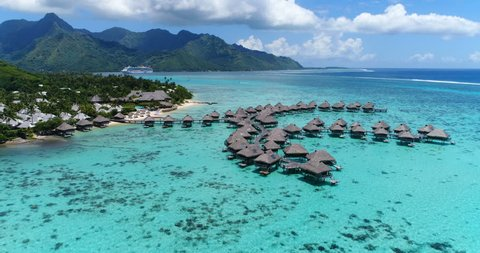 Tropical vacation paradise island with overwater bungalows resort in coral reef lagoon ocean by beach. Aerial video of Moorea, French Polynesia, Tahiti, South Pacific Ocean.