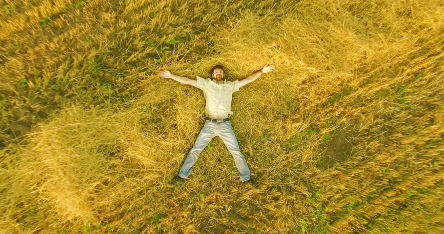 Aerial UHD 4K view. Vertical motion flight over formalwear man lying on yellow wheat field at sunny summer day. Top view on handsome relaxing man. | Shutterstock HD Video #26563928