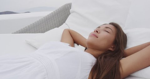 Asian woman relaxing sleeping beautiful and comfortable outdoor on daybed sun chair lounger with head on pillow on summer terrace enjoying luxury home living.