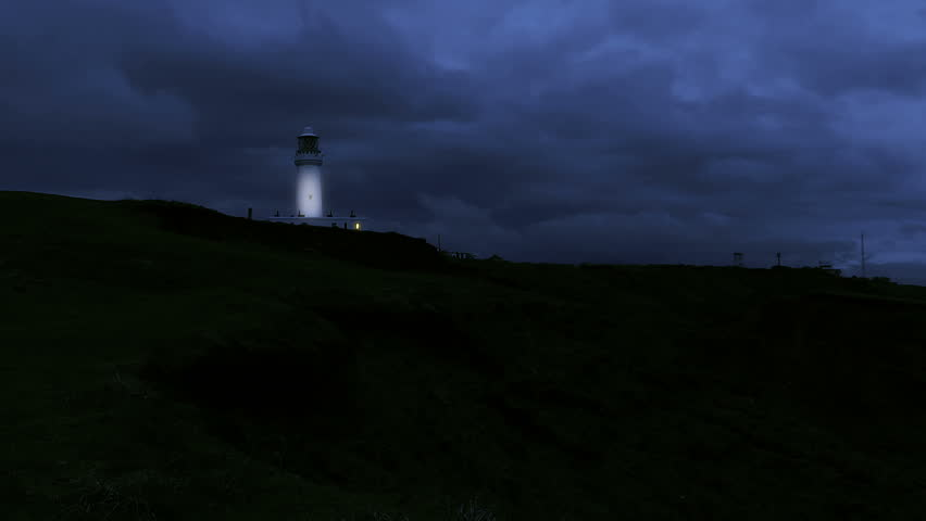 Lighthouse with flashing light at night stock footage. A distant Lighthouse on a cliff top with a rotating light set against a stormy looking night sky.