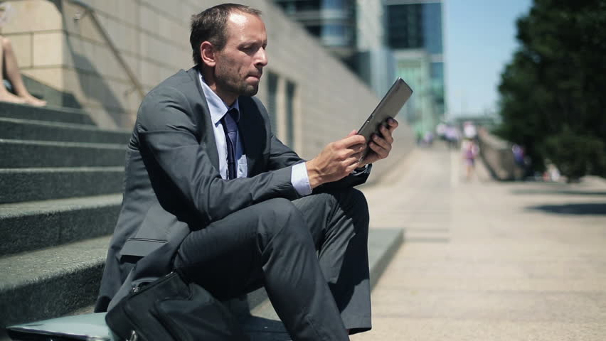 Businessman reading news on tablet computer in the city    Shutterstock HD Video #2660558