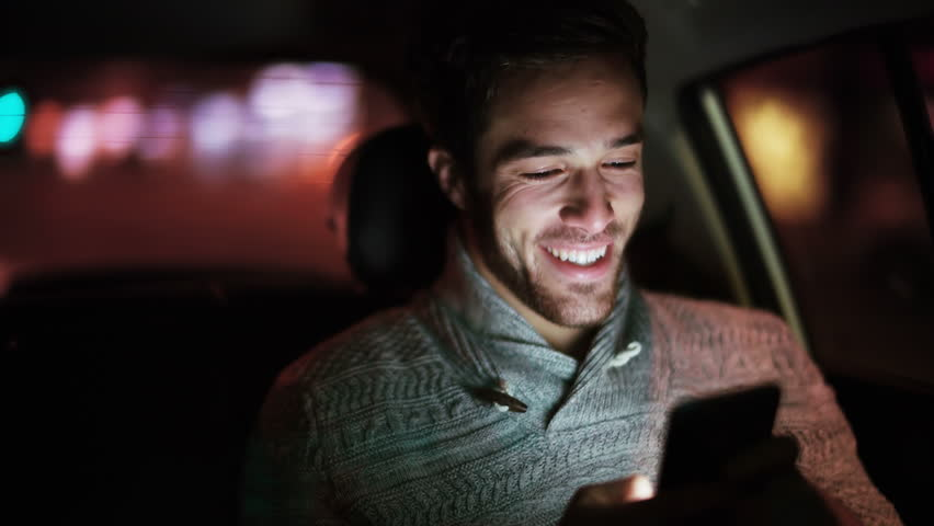 Handsome young man using cell phone in a car. He is texting, checking mails, chats or the news online. Night.