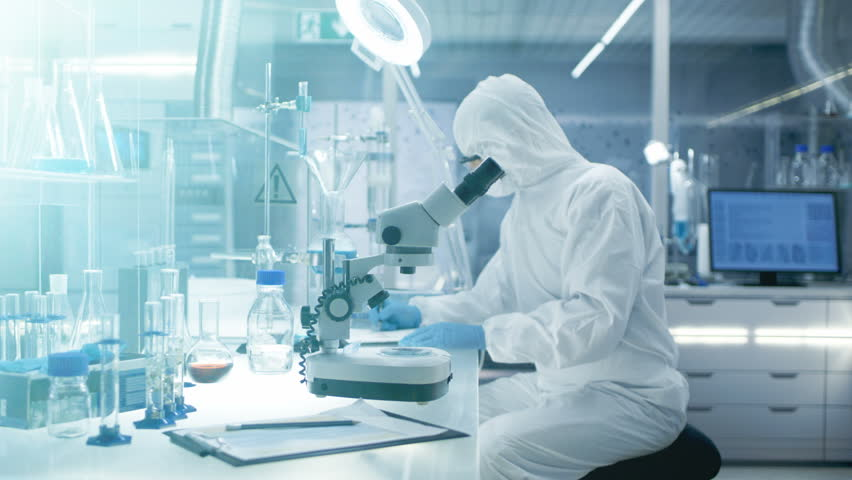 In a Secure High Level Laboratory Scientists in a Coverall Conducting a Research. Chemist Adjusts Samples in a Petri Dish with Pincers and then Examines Them Under Microscope.RED Cinema Camera