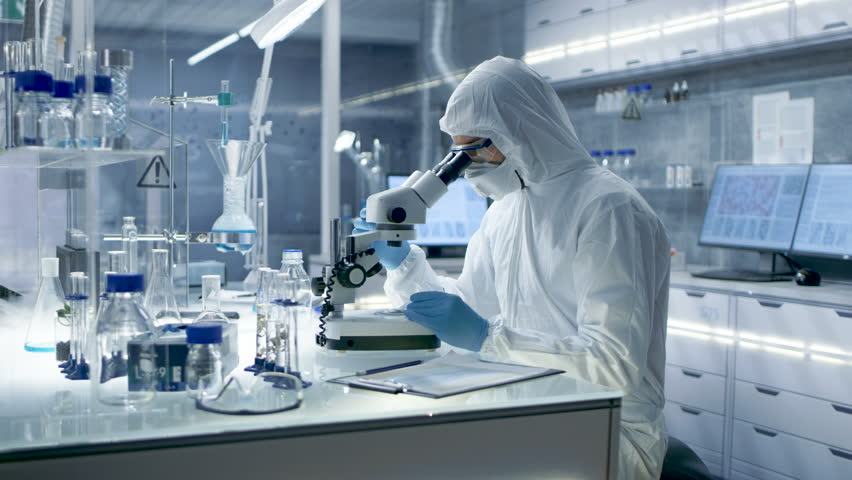 In a Secure High Level Research Laboratory Scientist in a Coverall Examines Petri Dish Under Microscope. Shot on RED EPIC-W 8K Helium Cinema Camera.