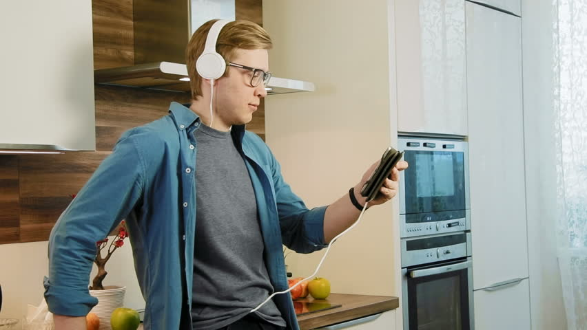Young laughing man watching streaming movie on digital tablet eating cereals with headphones | Shutterstock HD Video #26675698