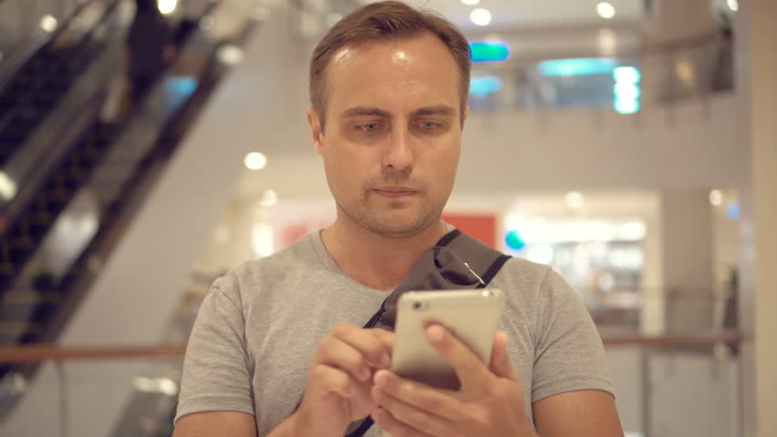 Young guy standing in shopping mall using smartphone, browsing, reading news, chatting with friends | Shutterstock HD Video #26679508