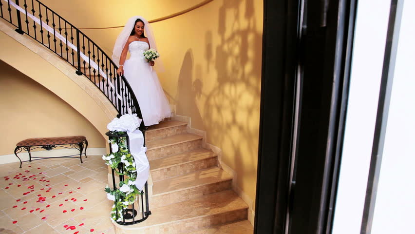 Beautiful African American bride wedding dress and veil descending marble staircase