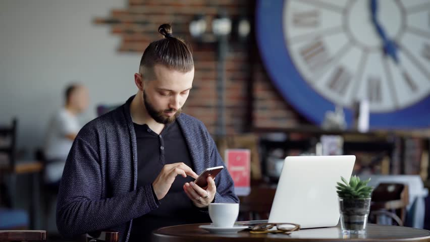 An adult guy drinks coffee in a modern cafe, a man with a hair tucked into his tail browses the latest news on the Internet on his mobile phone, there is a laptop on the desk - 4K stock footage clip