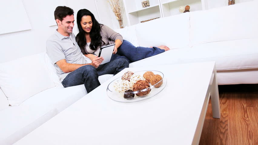 Casual heterosexual Hispanic couple using modern wireless tablet home sofa