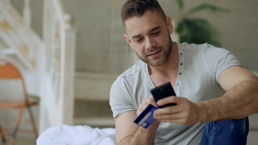 Attractive young man with smartphone and credit card shopping on the internet sit on bed at home   Shutterstock HD Video #26741488
