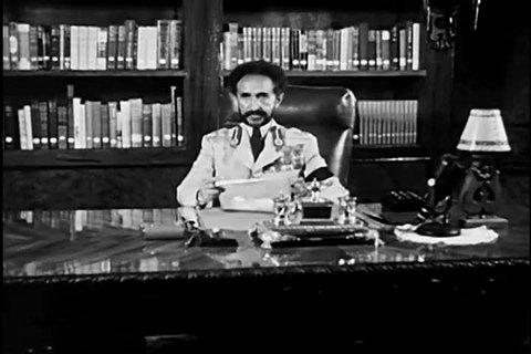 1950s: Haile Selassie I, Emperor of Ethiopia, reads a statement of gratitude to doctors, at his palace in Addis Ababa, with his pet lion, in 1958.