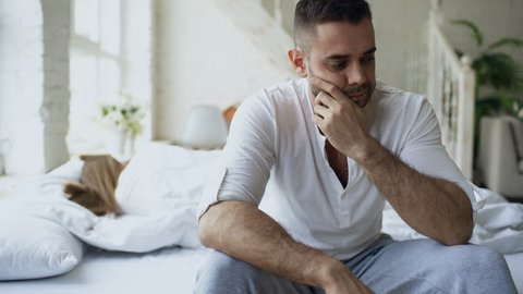 Upset young man sitting in bed have problems with sex while his girlfriend sleep in bedroom at home