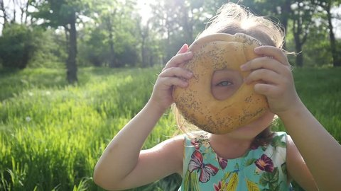 Cute Little Girl Play With Bagel Dough Product Nature Green Park Picnic In Sun Light Haze