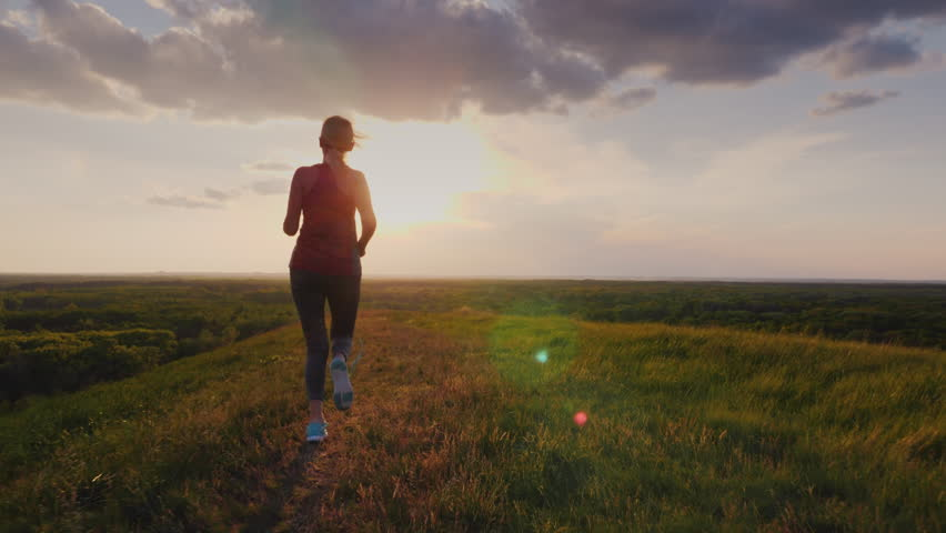 A close target - a woman runs down the hill in a picturesque place. She was tired, her lace on the sneaker untied. Concept - forward movement, purposefulness, victory