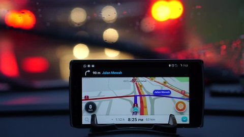 KUALA LUMPUR, MALAYSIA, May 15, 2017: GPS gadgets used when driving a car. wiper function when it rains at night with blurry lights background