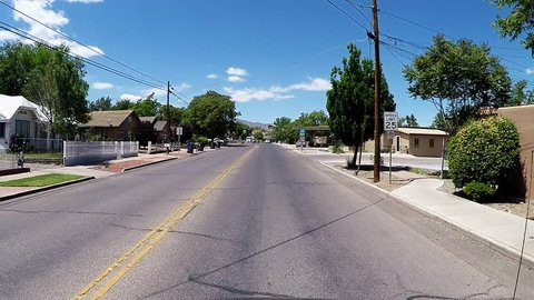 COTTONWOOD, AZ/USA: April 20, 2017- Car view driving shot in Cottonwood Arizona. Clip reveals a view passing by homes and other living quarters along a street in small town.