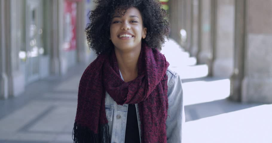 Attractive African girl in scarf with short curly hair posing with hands up and looking cheerfully at camera on background of street.
