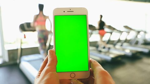 Mobile phone with green chroma key screen in vertical orientation in sport club with woman  runners using Treadmills. video footage
