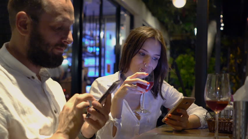 Young Couple Using Smartphones And Drinking Wine In Cafe At Night