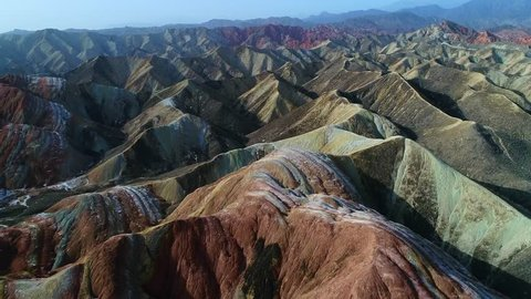 Flying a drone over the colorful Zhangye Rainbow Mountains; aerial view on sandstone hills and mountain chains covered by amazing pattern. Part 2 of a continuous 5 part series