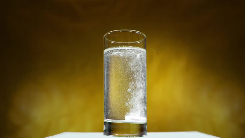 Aspirin tablet dissolves in water on a yellow background | Shutterstock HD Video #26852698