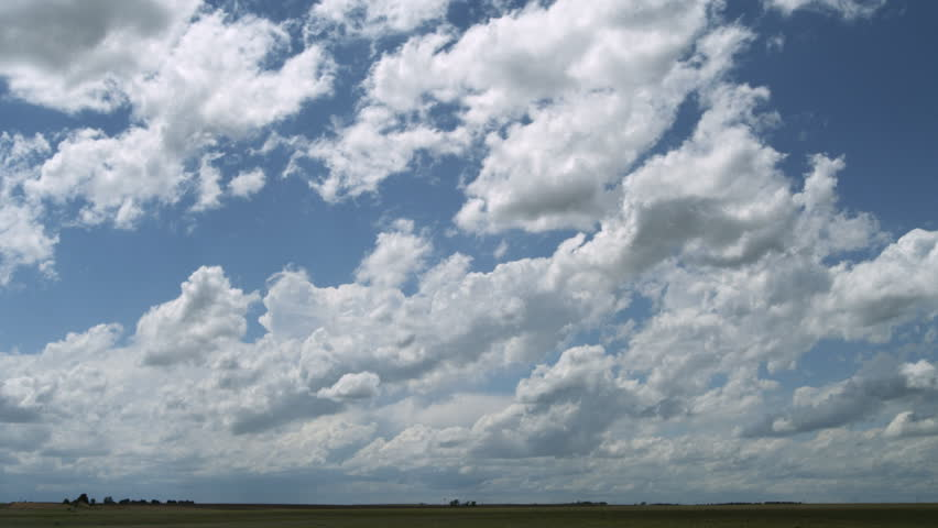 Cumulus clouds and distant storm with anvil top over prairie landscape