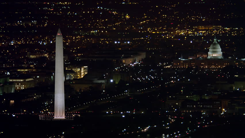 Over Washington DC cityscape at night, Washington Monument and Capitol in distance. Shot in 2011. | Shutterstock HD Video #26876914