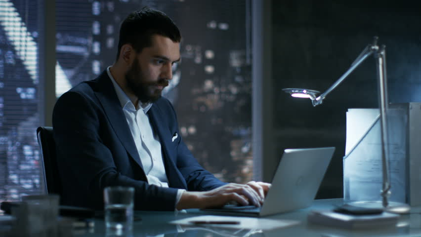 Late at Night in Private Office Businessman Works on a Laptop. He Succeeded Internationally by Winning Big Contract. He's Very Happy.