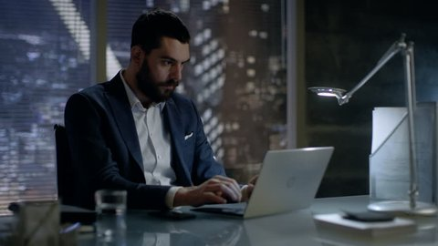 Late at Night Businessman Works on a Laptop in His Private Office with Big City Window View. Shot on RED EPIC-W 8K Helium Cinema Camera.