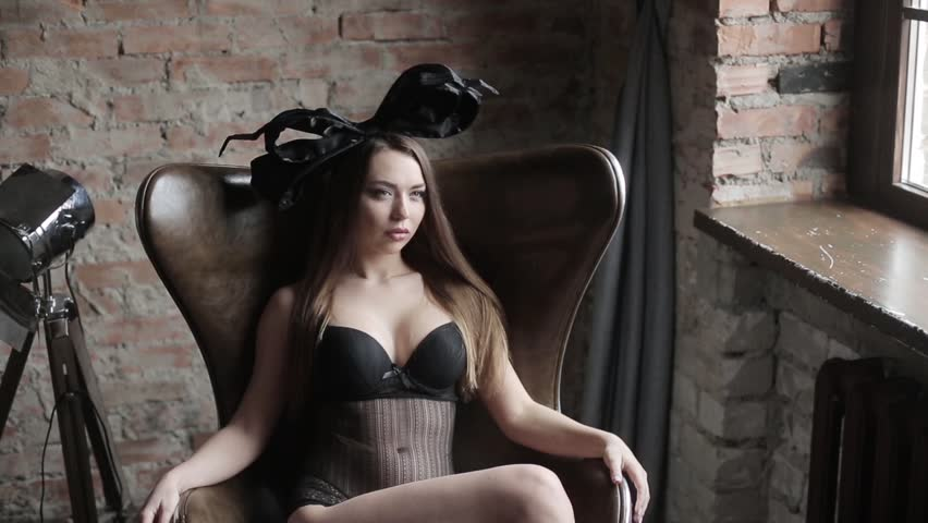 Beautiful sexy lady in elegant black bodysuit and bow. Close up fashion portrait of female model indoors. Beauty brunette woman with attractive body in lace lingerie. | Shutterstock HD Video #26898088