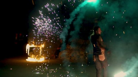 An amazing fire show at night. A man spinning fire. Long shot