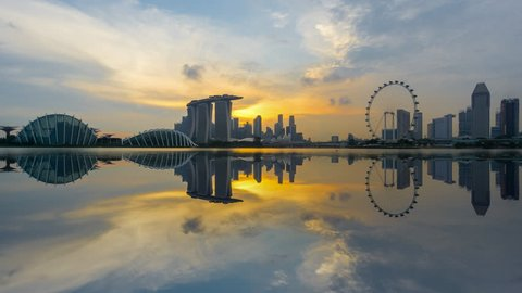 Beautiful Time lapse of Day to Night of Singapore skyline with reflection. 4K UHD. Pan Down Camera Motion.