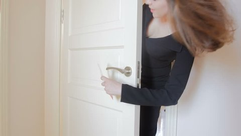 4K video of young passionate couple entering hotel room and hanging do not disturb sign on door