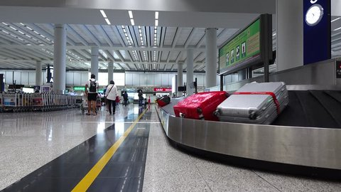 Few large bags move on conveyor belt, luggage claim hall of modern airport, rather empty space. Two people come away, baggage carousel turn ahead. Hong Kong International airport arrival area