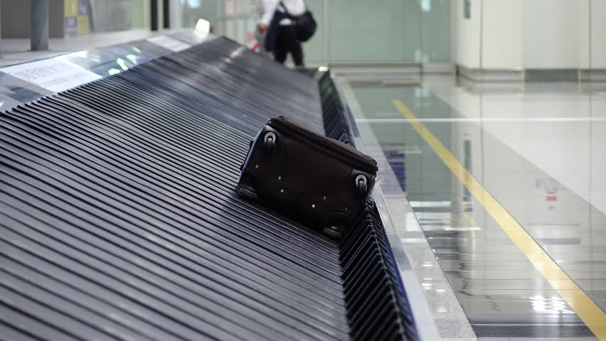 Passenger come and take suitcase from conveyor, luggage claim hall at modern international airport. Last bag lie on static carousel, man found his case, put it on floor and roll away | Shutterstock HD Video #26940328