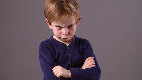 conflicted little 6-year old red hair child with arms crossed and dirty look showing his profile to express his frustration with an offended body language, grey background studio