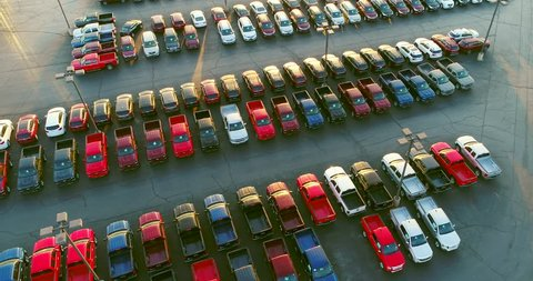 New car dealership lot, many vehicles for sale, aerial view.