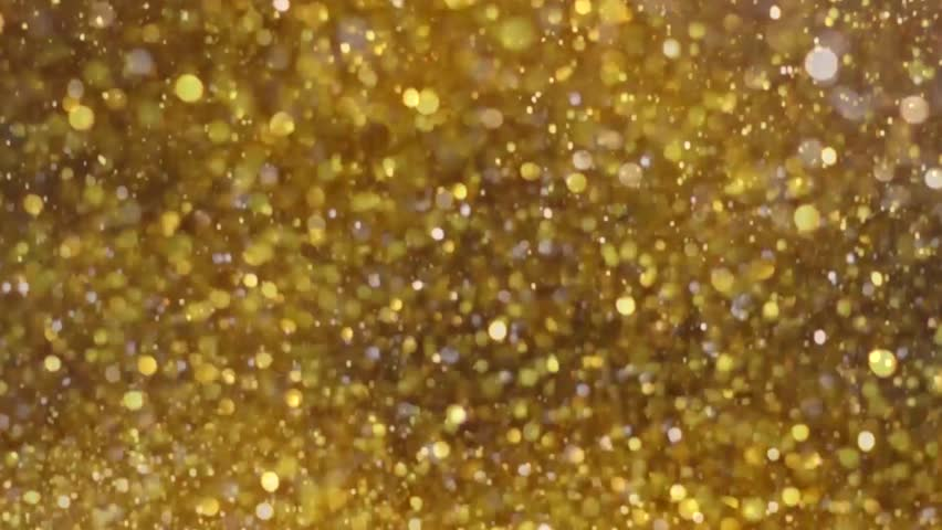 Big Explosion Golden Glitter Dust Tiny reflect light in the Air, Dark black background, Selective Focus close up blurred and slow motion, seamlless loop