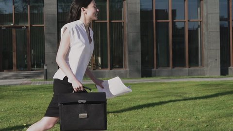 Asian Business Woman with Attache Case and Paper Documents in Hands is Running in the City. Steadicam stabilized 4K footage. Slow motion 100 fps
