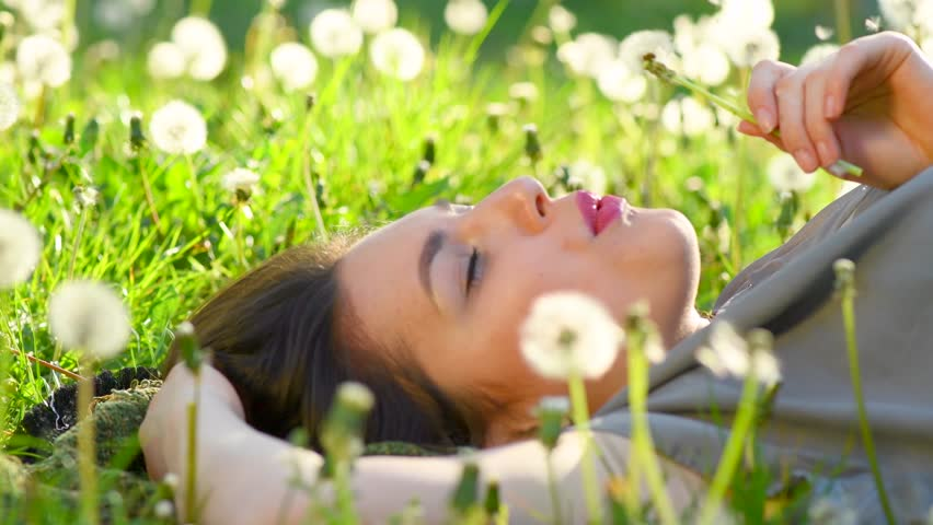 Beautiful Young Woman lying on the field in green grass and blowing dandelion. Outdoors. Enjoy Nature. Healthy Smiling Girl on spring lawn. Allergy free concept. 4K UHD video 3840X2160 #27024448